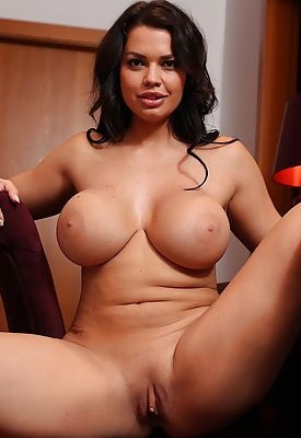 Busty and curvy brunette babe Chloe Lamoure strips naked.