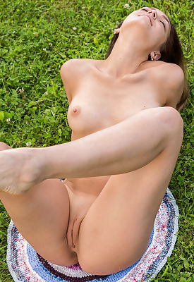 This hot busty babe shows every inch of her perfect body in the park with a great smile.